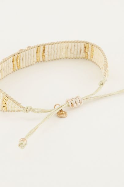 Witte kralenarmband met goudkleurige bedels
