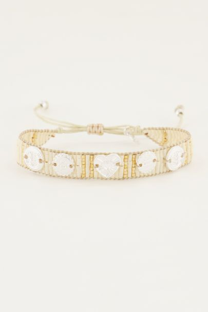 White beaded bracelet with silver charms